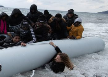 A volunteer is crashed under a dinghy as migrants from sub-saharan African countries arrive on a beach near the village of Skala Sikamias, after crossing part of the Aegean Sea from Turkey to the island of Lesbos, Greece, February 29, 2020. REUTERS/Alkis Konstantinidis