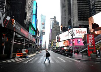A tourist crosses the 7th Avenue at Times Square on March 13, 2020 in New York City. (Photo by Johannes EISELE / AFP) (Photo by JOHANNES EISELE/AFP via Getty Images)